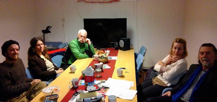 Bilden föreställer fem människor runt ett bord som tittar på fotografen.